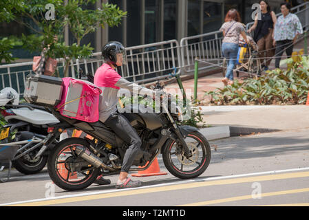 A motorcycle food courier in Singapore city - Stock Image