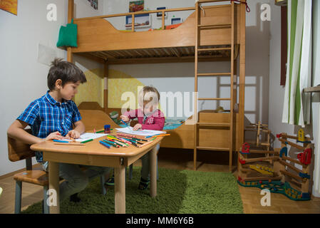 Little boy cutting a paper with scissor while older brother watches him, Munich, Germany - Stock Image