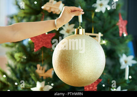 Closeup on big gold Christmas ball in a hand of trendy woman near Christmas tree - Stock Image