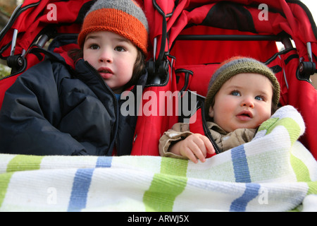 Two brothers sit in a double stroller on a cold winter day - Stock Image