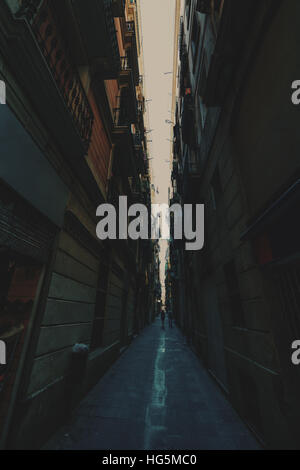 Wide angle view from bottom of dark narrow street in historical district of Barcelona - El Born: residential houses, - Stock Image