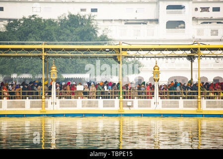 Tourists and pilgrims waiting in line at the entrance The Harmandir Sahib (Golden Temple). - Stock Image