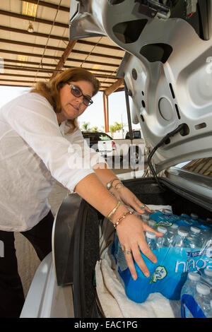 A women loads her car with water from a water charity in Porterville supplying bottled water to houses who have - Stock Image
