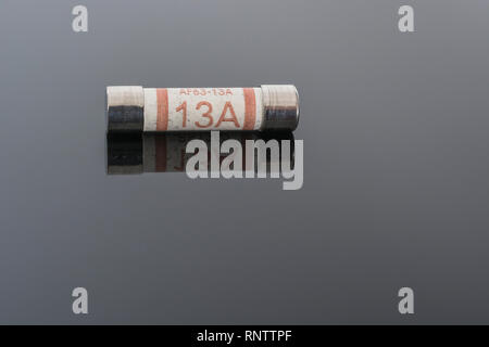 Domestic appliance electrical 13 Amp fuse (Ceramic Cartridge type) on reflective black background. Metaphor electrical safety. 25mm L x 6.3mm D - Stock Image