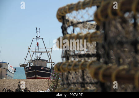 Hastings, UK -July 14 2018: Fishing nets and a boats docked boat on the pebbles beach of the port of Hastings on a hot summers day as the temperatures sore to above 27 degrees on 14 July 2018.  Hastings on the south coast of England is 53 miles south-east of London and is 8 miles from where the  Battle of Hastings took place in October 1066. Credit: David Mbiyu Credit: david mbiyu/Alamy Live News - Stock Image