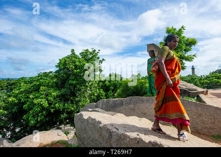 Elegance at the Monuments at Mahabalipuram near Chennai, India as women stroll in the countryside, protecting themselves from the sun with a parasol - Stock Image