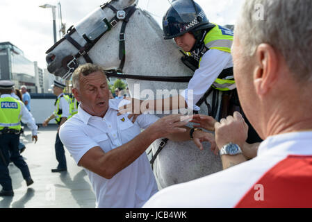 Chelsea fan held back by police officer outside the stadium at the FA Cup Final 2017 Chelsea vs Arsenal in Wembley. - Stock Image