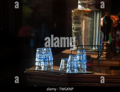 interior bar at the Grafton pub, kentish town, glasses and water dispenser lit by sunshine, - Stock Image