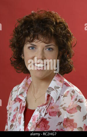 Happy portrait over 30 woman brown hair, red - Stock Image