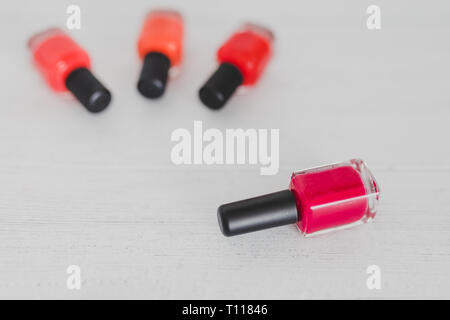 red nail polish bottle and other colors on wooden surface, concept of cosmetics industry and manicure - Stock Image