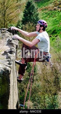 Rock clmber climbinng at Cratcliffe Tor near Elton, Winster, south of Bakewell extremely rural setting with a view - Stock Image