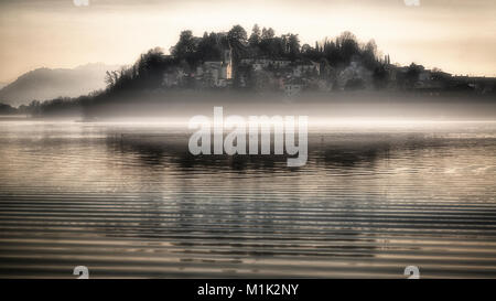 The little village of Biandronno with fog over the lake of Varese in a winter afternoon - Stock Image