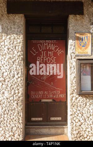 Sign on a door 'LE Lundi midi et le Dimanche je me repose. Du Lundi au samedi ouvert le sior & le midi' - Stock Image