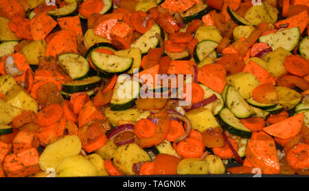 different raw oven vegetables on a baking tray, raw organic cutting oven vegetables flavored with various herbs and oil before baking - Stock Image