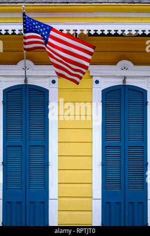 Front doors, exterior of a shotgun house with blue doors and American flag, downtown New Orleans, New Orleans French Quarter, New Orleans, Louisiana. - Stock Image