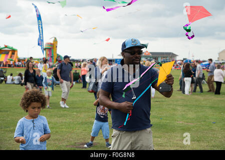 Portsmouth, UK. 15th August 2015. A man launches a string of kites as children look on at the International Kite - Stock Image