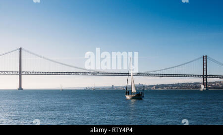 Sailboats with white sails on the Tagus River, 25 of April Bridge, Lisbon, Portugal. - Stock Image