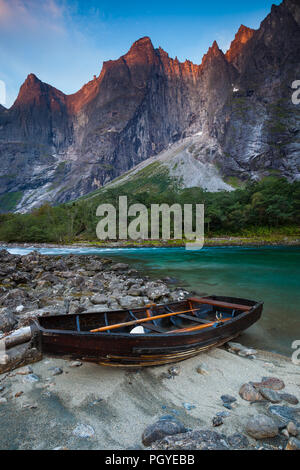 Row-boat beside Rauma River. In the background is the 3000 feet verical Troll Wall and the peaks Trolltindane, Romsdalen valley, Norway. - Stock Image