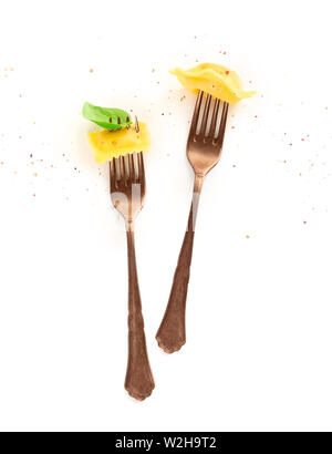 Two forks with different ravioli, basil leaf and pepper on a white background - Stock Image