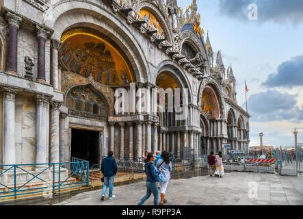 Tourists pass Saint Mark's Basilica Cathedral in Saint Mark's Square with the Columns of San Marco and San Todaro in view in Venice, Italy - Stock Image