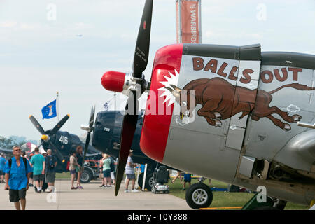 Visitors walk the line of warplanes at the airshow at Oshkosh, Wisconsin. - Stock Image