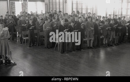 1950s, historical, pupils of the John Colet County Secondary school , Wendover, Bucks England, UK standing together in assembly with books open, possibly a bible. - Stock Image