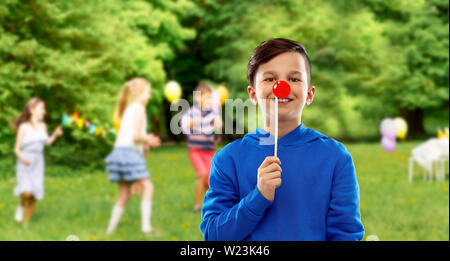 happy boy with red clown nose at birthday party - Stock Image