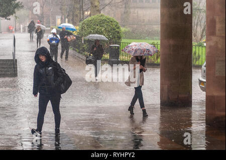 Coventry, West Midlands, UK. 14th March, 2019.  People rush to work in torrential rain which hit Coventry this morning. There will be showers and sunshine for the rest of the day.  Credit: Andy Gibson/Alamy Live News. - Stock Image