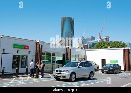 ASDA ATM cash withdrawals machine with people queuing, car park Crossharbour, Isle of Dogs, London Borough of Tower Hamlets. - Stock Image