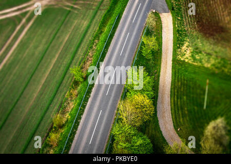 Highway asphalt road seen from above with trees and meadows along the roadside - Stock Image