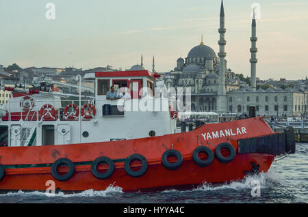 A tug boat sails into the Golden Horn at dusk.   The New Mosque (Yeni Camii) can be seen in the background. - Stock Image