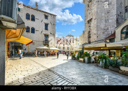 Tourists enjoy a sunny summer day at shops and cafes on the Fruit Square or Voćni trg, in the Diocletian's Palace section of Old Town Split, Croatia - Stock Image