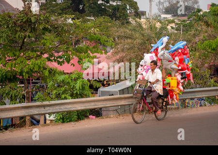 Elderly man transports his inflatable children toys via bicycle, Laos. - Stock Image
