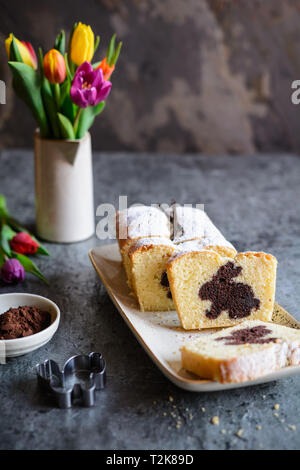 Sweet vanilla pound cake with Easter bunny inside, sprinkled with powdered sugar - Stock Image