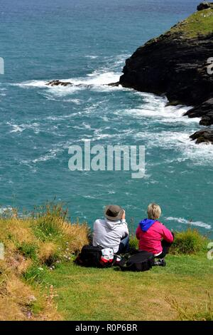 Male and female Photographer taking a photograph of the cornish coastline with camera and equiment bags behind him,Cornwall,England,UK - Stock Image