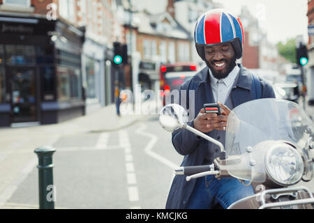 Smiling young businessman in helmet on motor scooter texting with cell phone on urban street - Stock Image