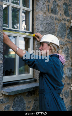 young female worker in hardhat measuring window frame of period dwelling under restoration - Stock Image