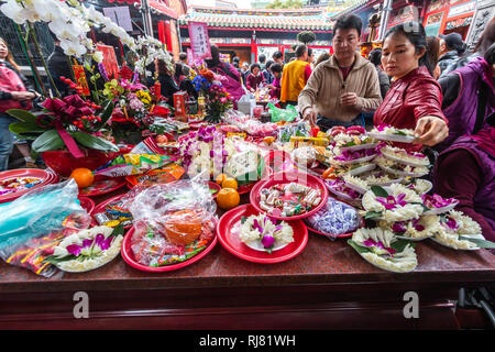 Taipei, Taiwan, Feb. 5, 2019: Visitors in Longshan Temple in Taipei places lotus flowers and other offerings on an offering table on Tuesday, Lunar New Year's Day, as they welcome the arrival of the Year of the Pig. Credit: Perry Svensson/Alamy Live News - Stock Image