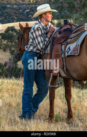 USA, California, Parkfield, V6 Ranch young cowboy standing by his horse leaning on his saddle (MR) - Stock Image