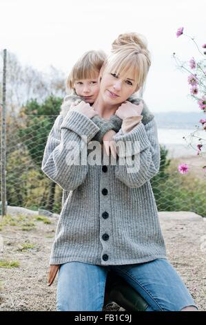 Portrait of boy with arms around mother in garden - Stock Image