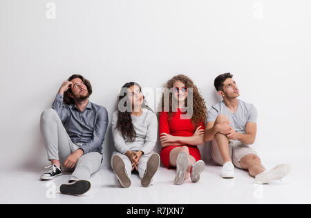 A happy young woman with a group of bored friends sitting on a floor in a studio. - Stock Image