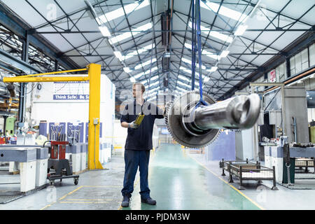 Engineer moving gear and spindle on crane in gearbox factory - Stock Image