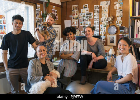 Portrait confident creative designers with dogs in office - Stock Image