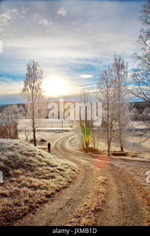 Man standing on a gravel driveway on a frosty autumn morning. - Stock Image