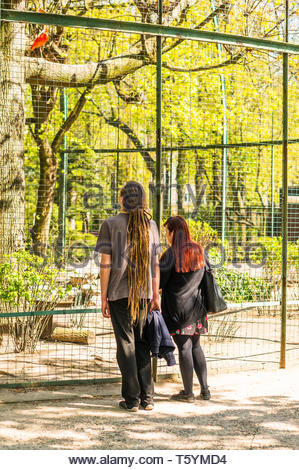 Poznan, Poland - April 18, 2019: Man with long dreadlocks and woman with red hair looking at birds behind a grid cage in the old zoo. - Stock Image