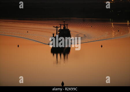 A small ship crousing during a sunset - Stock Image