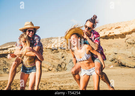Laughing a lot group of people enjoying and playing at the beach in summer holday vacation outdoor - alternative millennial have fun in friendship tog - Stock Image