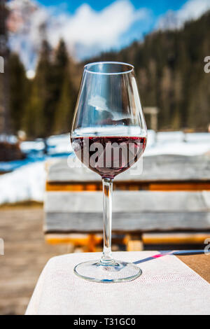 Picture of a glass of red Cabernet wine in a lodge in Cortina d'Ampezzo, Dolomites, Italy - Stock Image