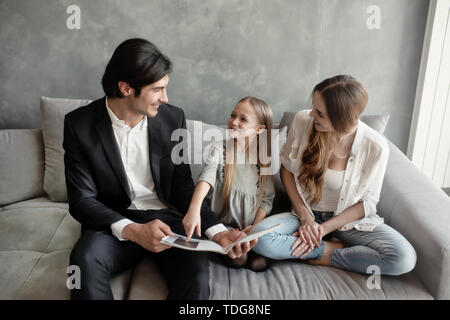 Happy little girl reads a book with her parents - Stock Image