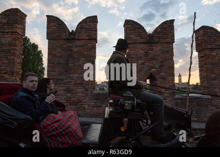 Tourists are guided by horse-drawn carriage in the center ofVerona, Italy - Stock Image